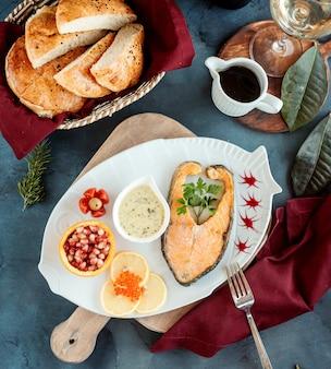 Vista superior de filete de salmón servido con salsa de hierbas, granadas y limones