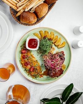 Vista superior de filetes de ternera servidos con papas fritas, ensalada y salsa de tomate