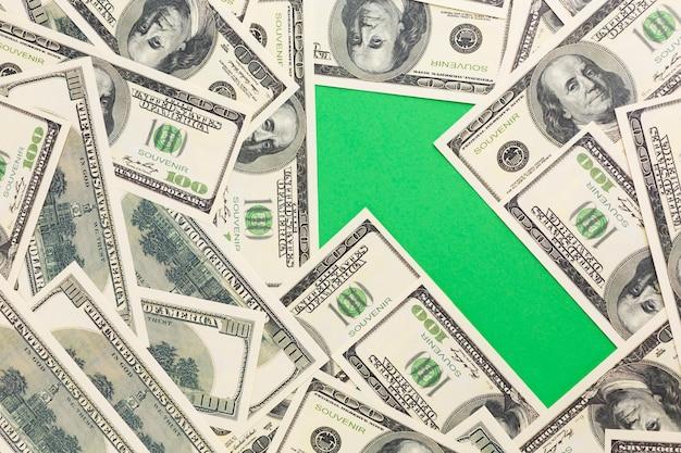 Vista superior de la flecha que muestra aumento con billetes