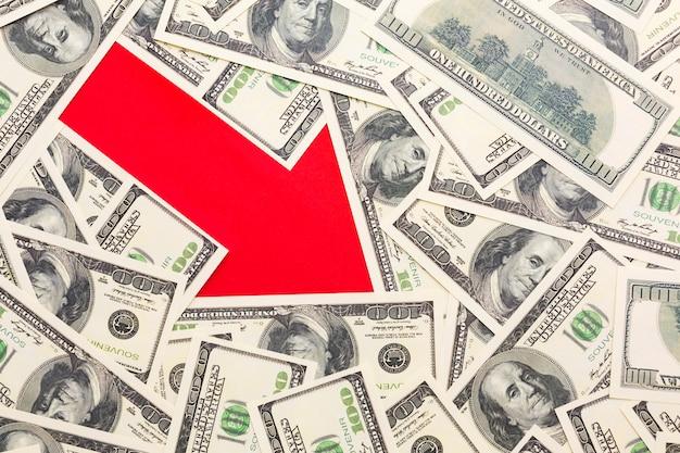 Vista superior de la flecha que muestra disminución con billetes