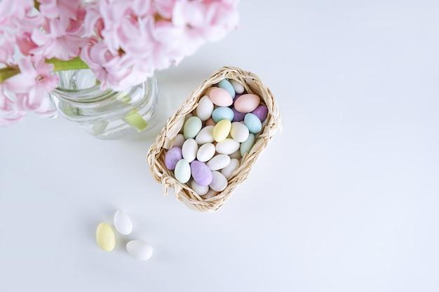 Vista superior de la flor elegante del jacinto en florero con los caramelos de los huevos de pascua en cesta en blanco