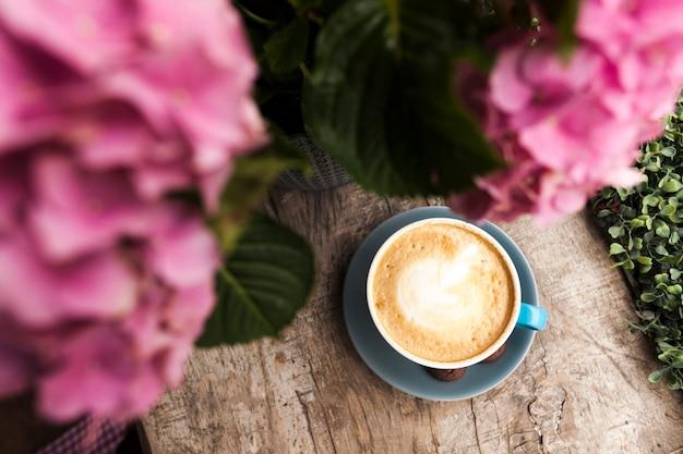 Vista superior de la flor rosada y sabroso café con espuma espumosa en superficie de madera