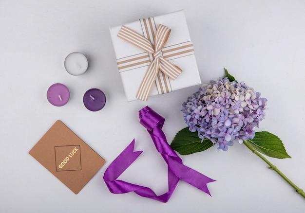 Vista superior de la flor con velas, caja de regalo de cinta y tarjeta de buena suerte sobre fondo blanco.