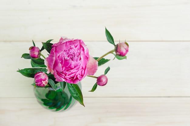 Vista superior de la floración hermosa peonía rosa fresca y brotes en florero sobre fondo de madera clara