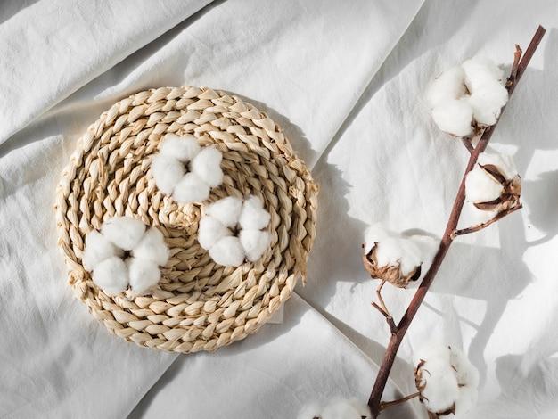 Vista superior de flores de algodón en sábana blanca