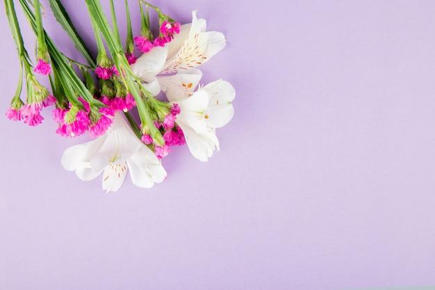 Vista superior de flores de alstroemeria y statice de color blanco y rosa sobre fondo lila con espacio de copia