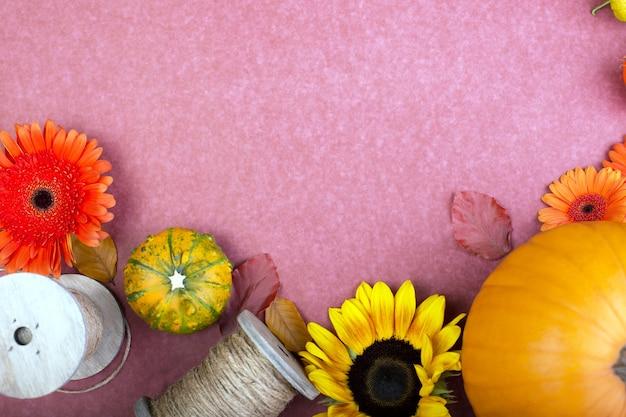 Vista superior de flores amarillas y naranjas, carrete de cuerda y calabazas sobre fondo rosa