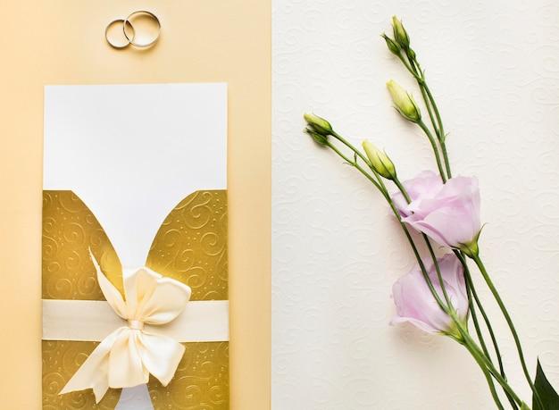 Vista superior de flores y anillos de papelería de boda de lujo.