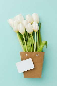 Vista superior de flores blancas de tulipán en una linda maceta de papel