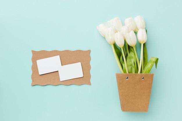 Vista superior de flores blancas de tulipán y tarjetas blancas vacías