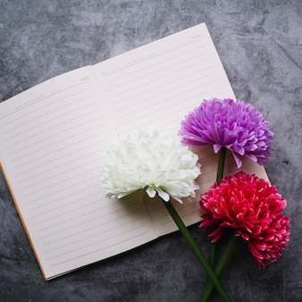 Vista superior de flores de crisantemo artificiales en una sola línea de cuaderno