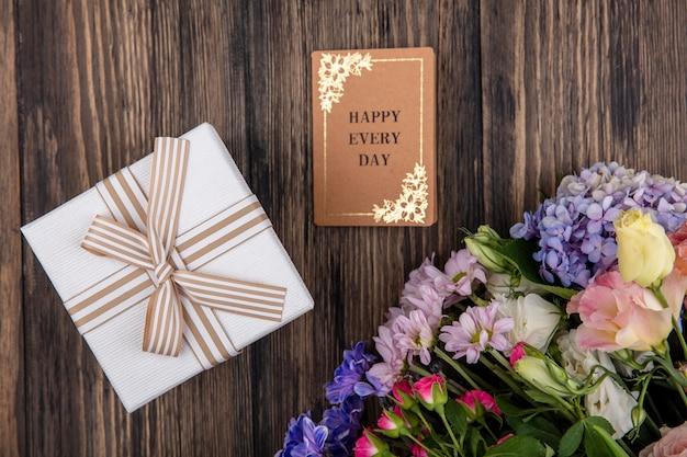 Vista superior de flores increíbles como margarita de rosas lilas con caja de regalo blanca sobre un fondo de madera