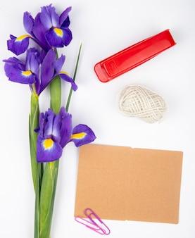 Vista superior de flores de iris púrpura oscuro con grapadora de cuerda roja y postal sobre fondo blanco