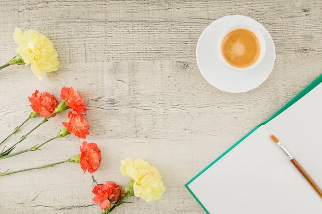 Vista superior flores con libro y café sobre fondo de madera