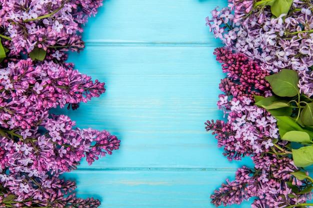 Vista superior de flores lilas aisladas sobre fondo de madera azul con espacio de copia