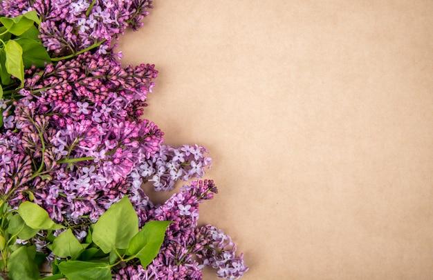 Vista superior de flores lilas aisladas sobre fondo de textura de papel marrón con espacio de copia