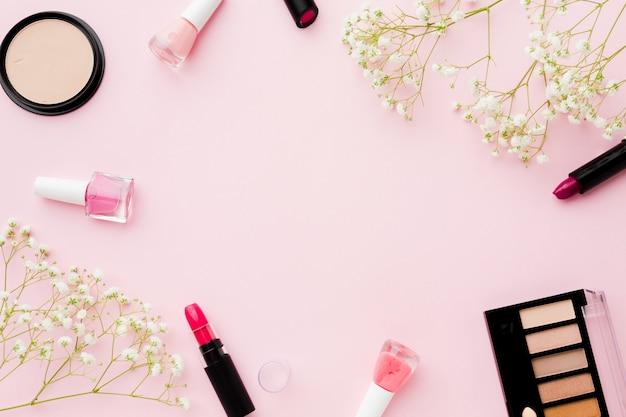 Vista superior de flores y maquillaje con espacio de copia