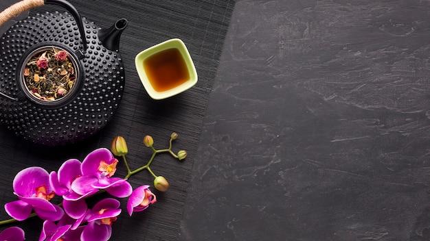 Vista superior de las flores de orquídeas rosadas y el té de hierbas en la estera de lugar sobre superficie negra