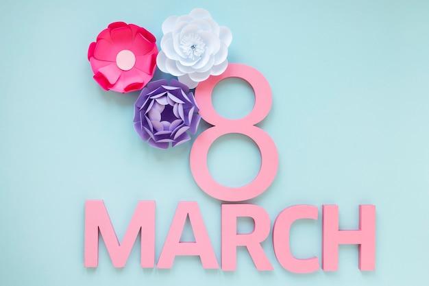 Vista superior de flores de papel y fecha para el día de la mujer.