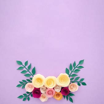 Vista superior de flores de papel y hojas sobre fondo morado
