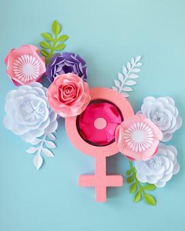 Vista superior de flores de papel con símbolo femenino para el día de la mujer