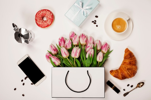 Vista superior de flores de primavera, café, teléfono móvil, cruasanes