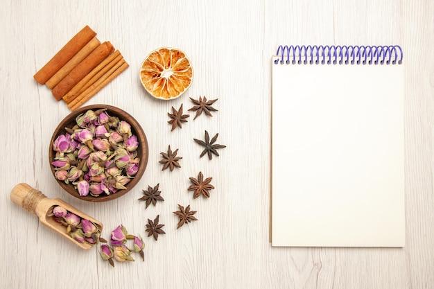 Vista superior de flores púrpuras con canela en el escritorio blanco color sabor a flor