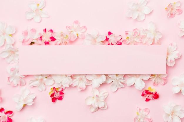 Vista superior flores sobre fondo rosa con papel en blanco