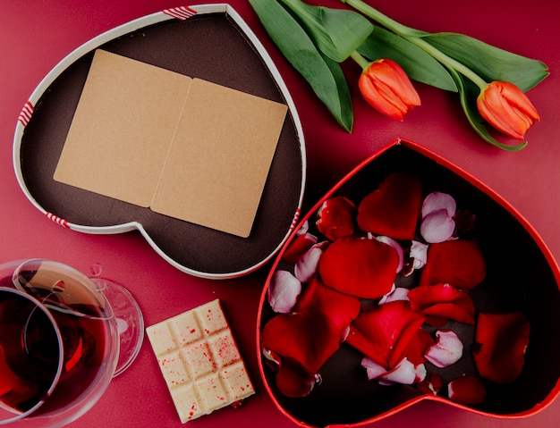 Vista superior de flores de tulipán de color rojo con caja de regalo en forma de corazón con una postal abierta y una caja llena de pétalos de rosa y chocolate blanco con una copa de vino sobre fondo rojo.