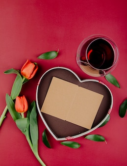 Vista superior de flores de tulipán de color rojo con caja de regalo en forma de corazón con una postal abierta y una copa de vino tinto sobre fondo rojo.