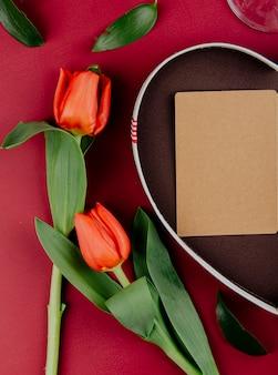 Vista superior de flores de tulipán de color rojo con caja de regalo en forma de corazón con una postal abierta sobre fondo rojo.