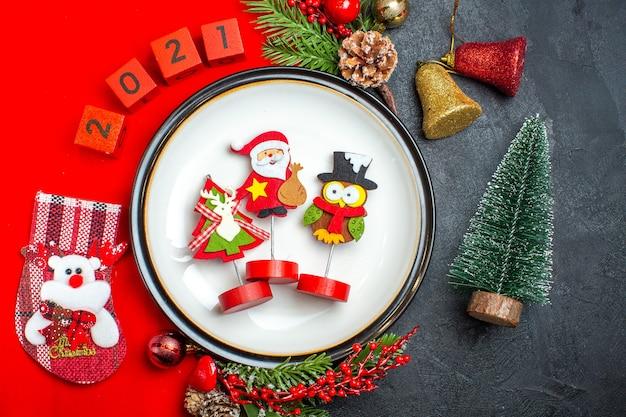 Vista superior del fondo de año nuevo con accesorios de decoración de plato de cena ramas de abeto y números calcetín de navidad en una servilleta roja junto al árbol de navidad en una mesa negra