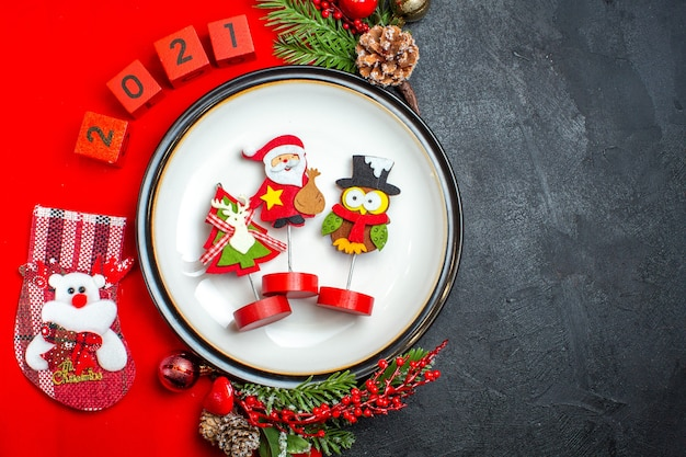 Vista superior del fondo de año nuevo con accesorios de decoración de plato de cena ramas de abeto y números calcetín de navidad en una servilleta roja sobre una mesa negra