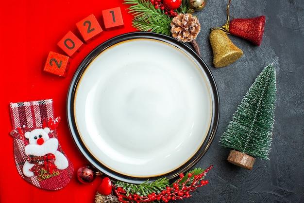 Vista superior del fondo de año nuevo con accesorios de decoración de plato de cena ramas de abeto y números en una servilleta roja junto al árbol de navidad en una mesa negra