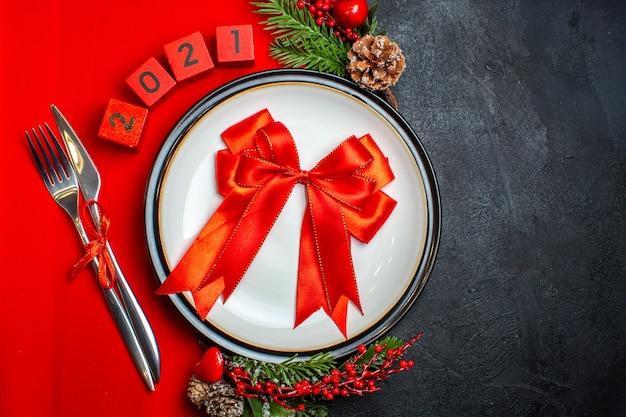 Vista superior del fondo de año nuevo con cinta roja en plato de cena cubiertos accesorios de decoración ramas de abeto y números en una servilleta roja sobre una mesa negra