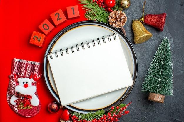 Vista superior del fondo de año nuevo con cuaderno en accesorios de decoración de plato de cena ramas de abeto y números en una servilleta roja junto al árbol de navidad en una mesa negra