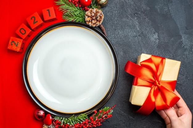 Vista superior del fondo de año nuevo con plato de cena y accesorios de decoración de regalo ramas de abeto y números en una servilleta roja sobre una mesa negra