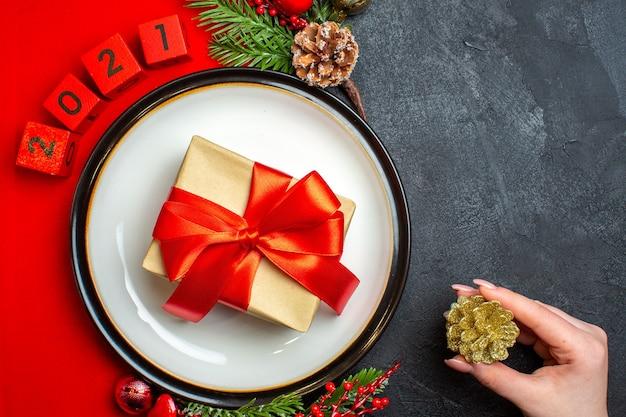Vista superior del fondo de año nuevo con regalo en accesorios de decoración de plato de cena ramas de abeto y números en una servilleta roja sobre una mesa negra