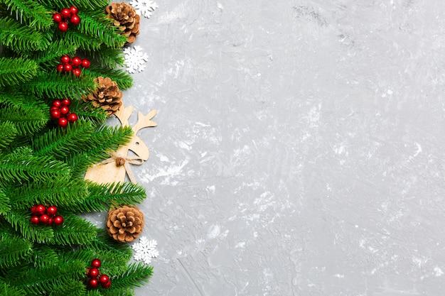 Vista superior del fondo de navidad hecho de abeto y decoraciones sobre fondo de cemento. concepto de vacaciones de año nuevo con espacio de copia