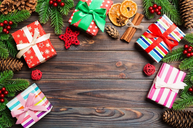 Vista superior del fondo de navidad hecho de abeto, regalos y otras decacciones sobre fondo de madera. concepto de vacaciones de año nuevo con espacio de copia