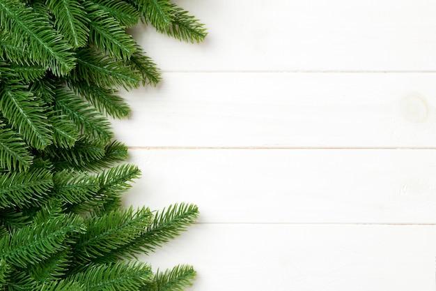 Vista superior del fondo de navidad hecho de ramas de abeto. concepto de año nuevo con espacio de copia sobre fondo de madera.