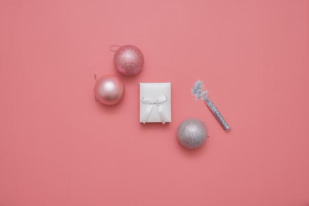 Vista superior de fondo rosa con bolas y caja de esencia