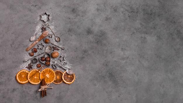 Vista superior de la forma del árbol de navidad hecha de cítricos secos y utensilios de cocina