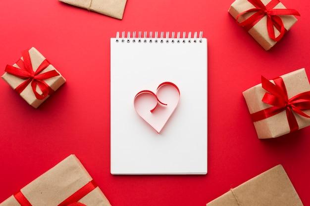 Vista superior de la forma del corazón de papel en el cuaderno con regalos