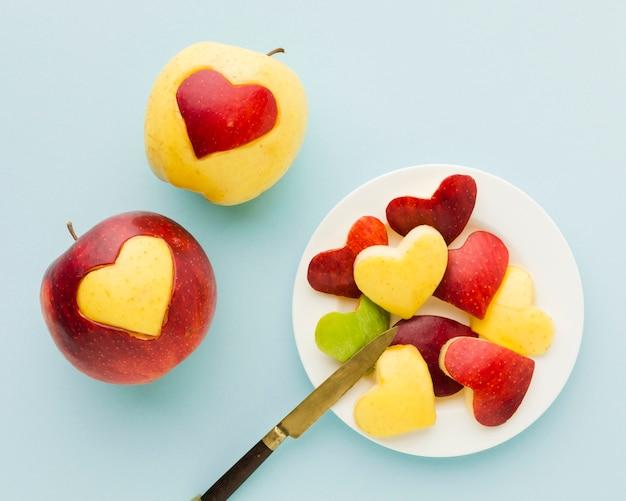 Vista superior de las formas de corazón de fruta en un plato con cuchillo