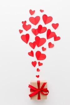Vista superior de formas de corazón de papel y regalo para el día de san valentín