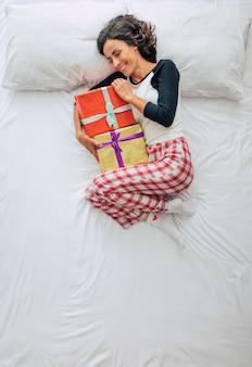 Vista superior foto de cuerpo entero de una hermosa joven morena rizada en ropa casual con cajas de regalo en las manos. soñando y relajándose