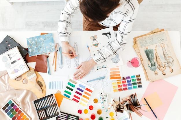 Vista superior foto recortada de mujer joven ilustrador de moda dibujo
