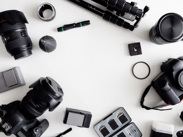 Vista superior del fotógrafo del espacio de trabajo con cámara digital, flash, kit de limpieza, tarjeta de memoria, trípode y accesorio de cámara sobre fondo blanco de mesa