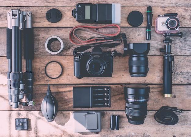 Vista superior del fotógrafo del espacio de trabajo con cámara digital, flash, kit de limpieza, tarjeta de memoria, trípode y accesorio de cámara sobre fondo de mesa de madera